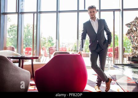 Cleverer Geschäftsmann gekleidet, lächelnd im Büro - Stockfoto