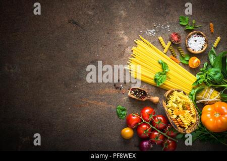 Italienisches Essen Hintergrund. Teigwaren Tomaten Basilikum. Zutaten zum Kochen. - Stockfoto
