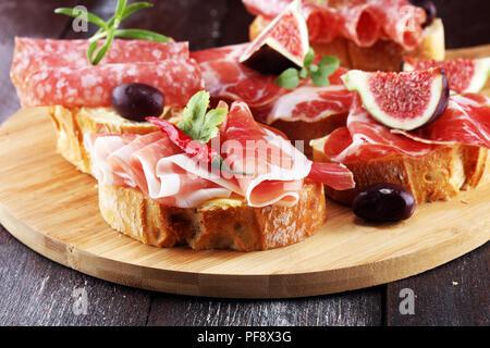 Sandwich mit Schinken oder Salami oder crudo. Antipasti gourmet bruschetta Snack - Stockfoto