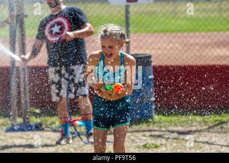 Sommer Spaß, im Wasser kämpfen. Younng blonde Mädchen, in Shorts und Badekleidung und lachte, als sie gespritzt wird. Model Released