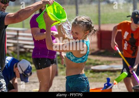 Sommer Spaß, im Wasser kämpfen. Younng blonde Mädchen, in Shorts und Badekleidung und lachte, als sie Eimer Wasser wird auf sie entleerte. Model Released