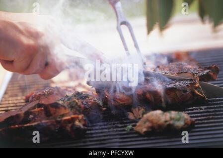 Fleisch grillen am Grill werden von Hand geschnitten mit Messer und Gabel, bis zu schließen. - Stockfoto