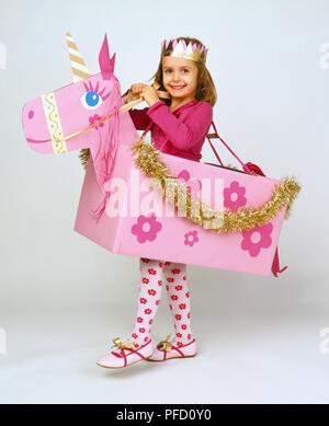 Lächelnde Mädchen mit langem Haar, tragen rosa Shirt, rosa Strumpfhose mit Blumenmuster und pink-goldenes Papier Krone, um die Schultern Gurt, stehend in rosa Pappe Pferd mit gold Dekoration, Beine unter klemmt - Stockfoto