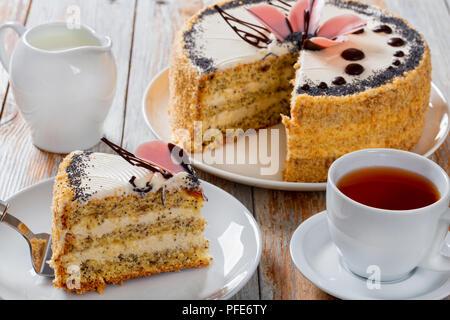Biskuitteig mit Mohn mit Creme mit ein ausgeschnittenes Stück Kuchen Schaufel auf dem weißen Teller schließen 2-in-1-up mit Krug Milch, Tasse mit schwarzem Kaffee auf dem sa - Stockfoto