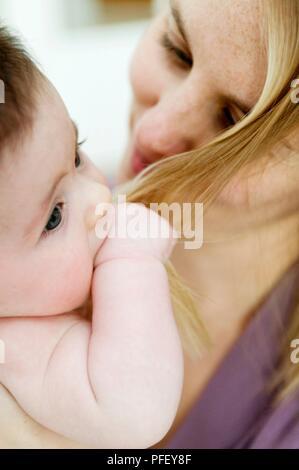 Baby girl Holding Strang der blonden Frau Haar, close-up - Stockfoto