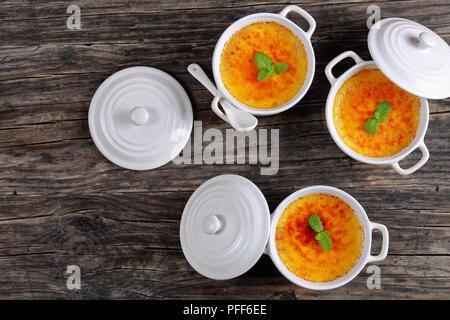 Köstliche Crème Brûlée - Französische dessert Pudding mit harten Karamell oben, mit Minze aus weisser Keramik souffle Gerichte eingerichtet, authentische Rezept