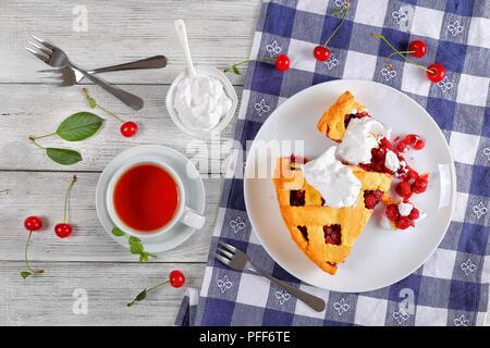 Scheiben köstliche hausgemachte Sour Cherry Pie an der Platte. Schüssel mit Schlagsahne, Dessert gabeln, Tasse Tee auf Küche Tuch, klassisches Rezept, Ansicht von - Stockfoto