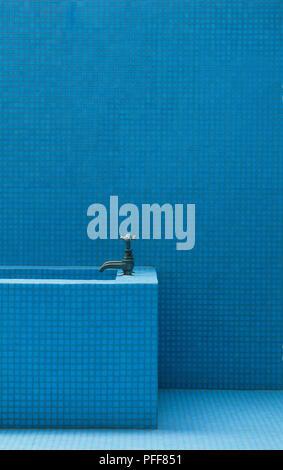 Badezimmer Wände, Boden und oberen Ende der rechteckige Badewanne mit Bronze farbigen Armaturen, mit identischen, winzigen blauen Fliesen bedeckt - Stockfoto