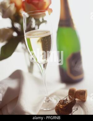 Glas Champagner mit einer Flasche unscharf im Hintergrund. - Stockfoto