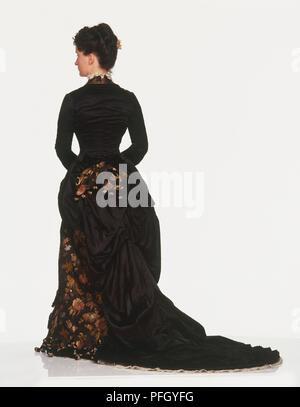 Eine Frau im späten 19. Jahrhundert treiben Kleid aus Seide in der Farbe dunkel mit floralen Mustern, Ansicht von hinten - Stockfoto