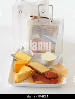 """Auswahl der Milchprodukte einschließlich Red Leicester, """"Jarlsberg"""" und """"Greyerzer Käse, Butter, Frischkäse und rotes Fleisch auf einem Tablett, neben Taschen, eine enthält ein Magazin - Stockfoto"""