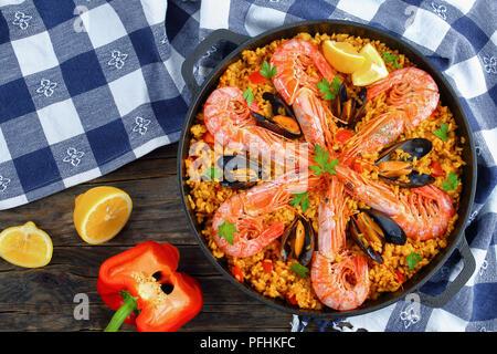 Köstliche Meeresfrüchte Valencia Paella mit Gambas, Muscheln auf herzhafte cremige Safran Reis mit Gewürzen und Zitrone Keile in der Wanne, auf hölzernen Tisch, Blick f - Stockfoto