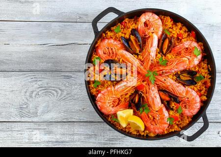 Köstliche Meeresfrüchte Valencia Paella mit Gambas, Muscheln auf herzhafte cremige Safran Reis mit Gewürzen und Zitrone Keile in der Wanne, auf alten Holztisch, au - Stockfoto