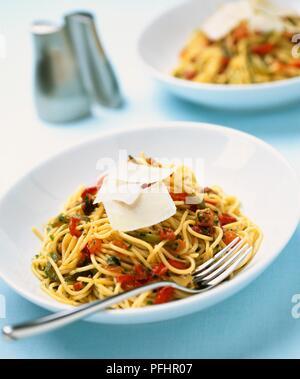 Schüssel Spaghetti mit gehackten Tomaten, Kräutern und Parmesan, und eine Gabel, close-up - Stockfoto