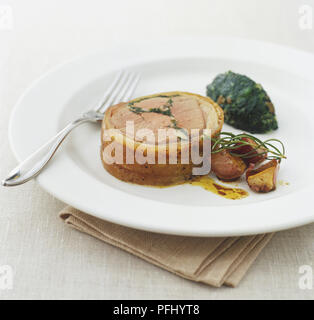 Braten gefüllter Lammrücken serviert mit Spinat und gerösteten Knoblauch garniert mit Rosmarin - Stockfoto