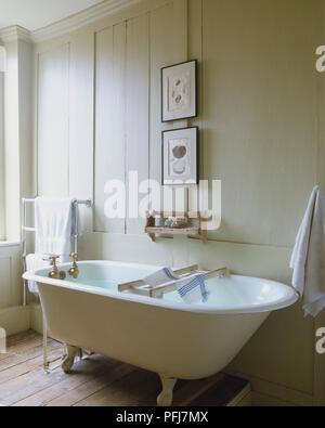 Badezimmer mit weißen holzgetäfelten Wänden, gerahmten Zeichnungen von Muschelschalen und kleine Holz- Seife Regal über ovale Badewanne mit ornamentalen Füße, bronze Hähne, weiße Handtücher auf Metall Handtuchhalter, dunklen Holzboden - Stockfoto