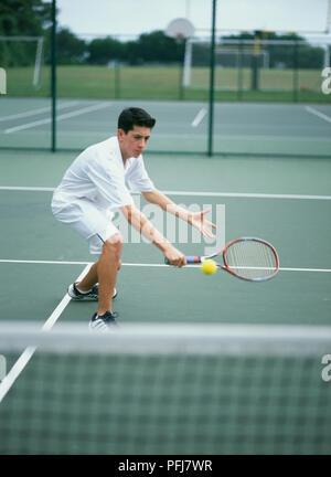 Junge in weißen Tennis Kleidung nach vorne beugen, die Schläger vor ihm, gelbe Kugel in der Luft - Stockfoto