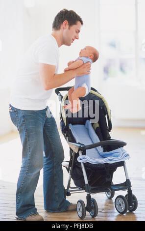 Junger Mann baby Herausheben der Buggy, Seitenansicht. - Stockfoto