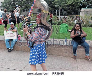 Frau Tubist in Clownesken patriotischer Kleidung fügt ein wenig Humor zu einer politischen Kundgebung in Freedom Park in Washington, D.C., USA. - Stockfoto