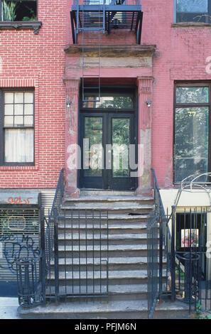 USA, New York, Detail der Fassade aus rotem Backstein Gebäude, das Öffnen der vorderen Tor und Schritte vor Glastür. - Stockfoto