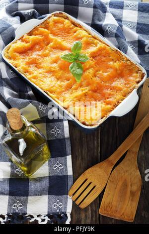 Köstliche italienische Lasagne Schichten mit Pasta und Bolognese ragout, gekrönt mit geschmolzenem Käse und frische Basilikumblätter in Auflaufform mit Küche - Stockfoto