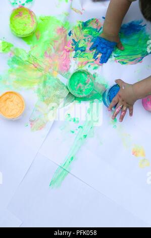 Der Toddler Hände mit Farbe verschmiert, Blatt Papier und Töpfe von Farbe, über dem Boden - Stockfoto