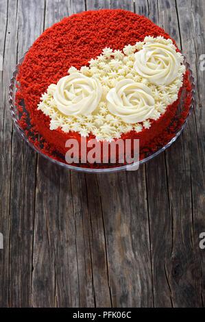 Delicious Red Velvet Cake mit schönen Creme Rosen dekoriert und mit roter Schwamm Kuchen Krümel auf die Platte an der alten, dunklen Holztisch sprengte, vertikale v - Stockfoto