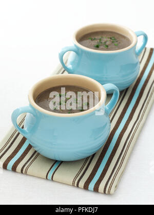 Pilzsuppe garniert mit gehackter Petersilie, in blau Keramik Schüsseln serviert mit Griffen, auf gestreiftem Tuch, close-up - Stockfoto