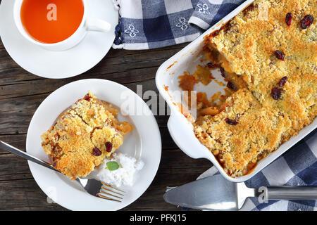 Lecker Apple Crumble oder Apple Crisp in Auflaufform und ein Teil auf Platte mit Kokosmilch. Tasse Tee an Hintergrund, Ansicht von oben, close-up - Stockfoto