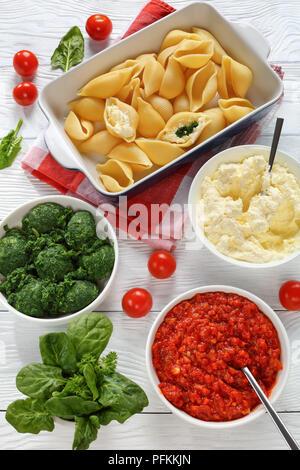Große pasta Muscheln im Bilden zu gefüllt mit Käse und Spinat. Sauce marinara, frische Spinatblätter, Weichkäse, gemischt mit geriebenen Mozzarella i - Stockfoto