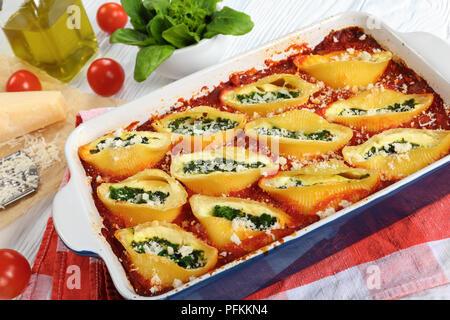 Köstliche gebackene conchiglion Pasta gefüllt mit cremiger Frischkäse und Spinat mit Parmesan in Auflaufform bestreut. geriebener Parmesan auf - Stockfoto