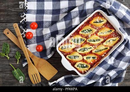 Schalenform Pasta gefüllt mit cremiger Frischkäse und Spinat mit Parmesan bestreut, in Auflaufform mit Küchentuch und Holzspatel auf - Stockfoto