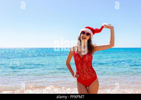 Junge Mädchen im roten Badeanzug und Weihnachten hat am Strand. - Stockfoto