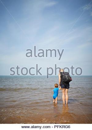 Mama und Baby Sohn im Meer mit Blick auf den Horizont, an einem sonnigen Tag am Strand während der Sommermonate mit blauem Himmel und warmen Sonne - Stockfoto
