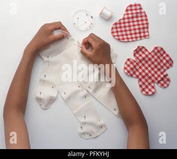 Die Rag Doll, Pinning die Puppe-förmiges Stück Stoff zusammen, mit überprüften Stück Stoff schneiden in der Nähe zu gestalten, close-up - Stockfoto