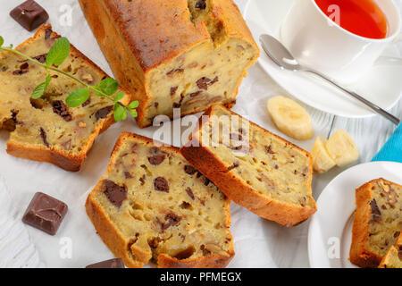 In der Nähe der frisch gebackene leckere Bananen Brot mit Nüssen und Schokolade Stücke in Scheiben schneiden auf Schneidebrett. Zutaten und Tasse Tee auf Woode - Stockfoto