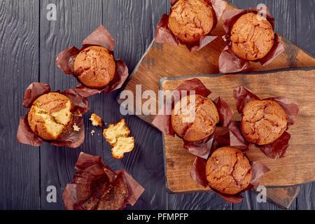 Leckere hausgemachte frische Muffins auf hölzerne Schneidbretter und man muss auf einen Tisch zerbröckelt, Ansicht von oben, flach - Stockfoto