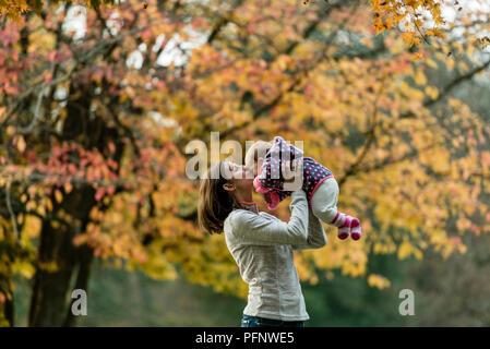 Herbst Szene von Mutter küssen junge Mädchen im Freien mit bunten Bäume im Park. - Stockfoto