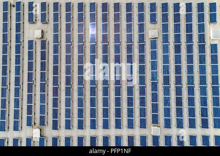 Luftbild von Oben nach Unten Blick auf viele Sonnenkollektoren Zeilen aufgereiht auf der werkseigenen Dach. - Stockfoto