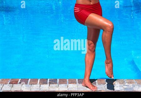 Frau im Bikini Bottoms, auf einem Bein stehen neben dem Pool, das andere Bein über das andere, close-up - Stockfoto