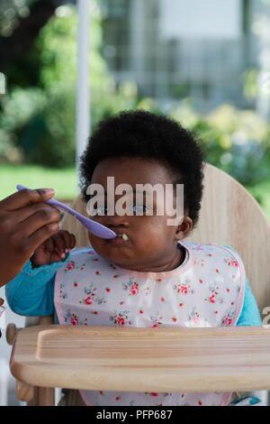 Baby Mädchen in hoher Stuhl mit Löffel, Frontansicht zugeführt wird eingesetzt - Stockfoto
