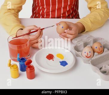 Mädchen Malerei blickt auf Ostereier, Töpfe von Lack und ei Box auf dem Tisch, Nahaufnahme - Stockfoto
