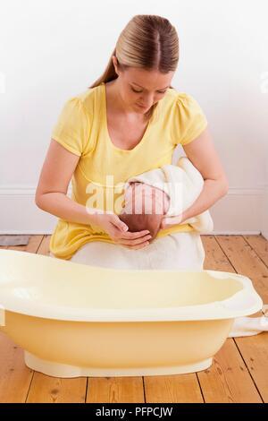 Mutter kniend auf Holzboden waschen Kopf von vier Wochen alten Baby boy in Handtuch über Baby Badewanne gewickelt - Stockfoto