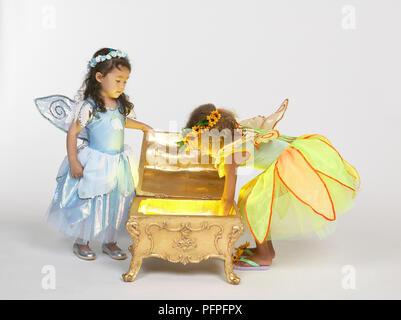 Zwei Mädchen in Fee Kostüm in einem goldenen Brust suchen - Stockfoto