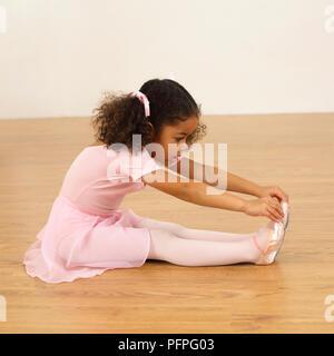 Mädchen in Ballerina Outfit sitzen auf dem Boden und berühren ihre Zehen, 4 Jahre alt - Stockfoto