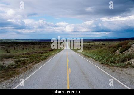 USA, Alaska, Western Denali Highway, gerade Straße durch Landschaft mit weißen Wolken und blauer Himmel über - Stockfoto