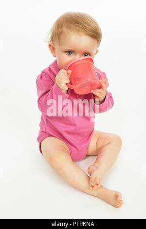 Baby in rosa Strampler trinken (Modell Alter - 9 Monate) - Stockfoto