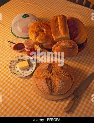 Frisches Brot, Käse, Butter, Konfitüre, Marmelade und Brot Messer auf karierte Tischdecke - Stockfoto
