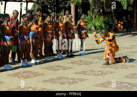 Young Zulu Mann in bunten kulturellen Kleid, vor einer Gruppe von traditionellen Straßenkünstler an uShaka, Durban, Südafrika - Stockfoto