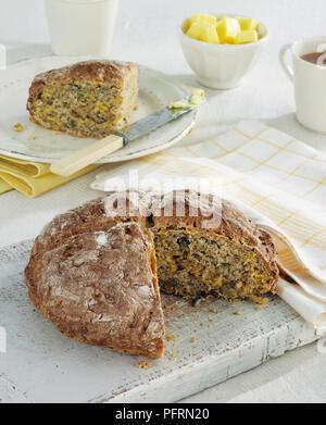 Soda Kürbis Brot auf Schneidebrett, Teller, Messer und Butter im Hintergrund - Stockfoto